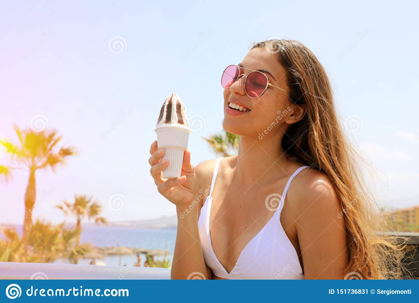 Beautiful girl with sunglasses eating ice cream on Tenerife beach in her travel holidays