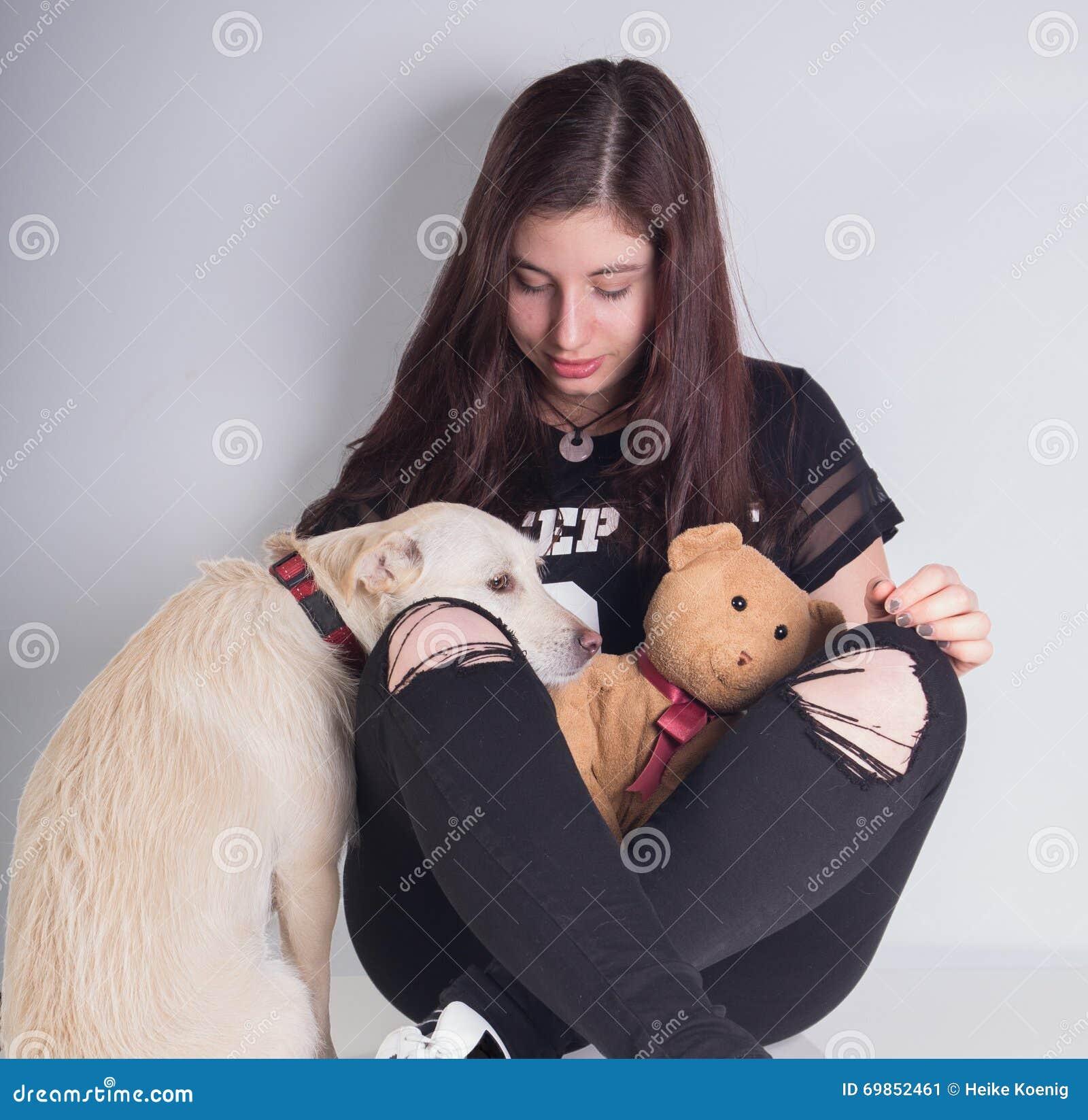 Beautiful girl with teddybear and sad looking dog