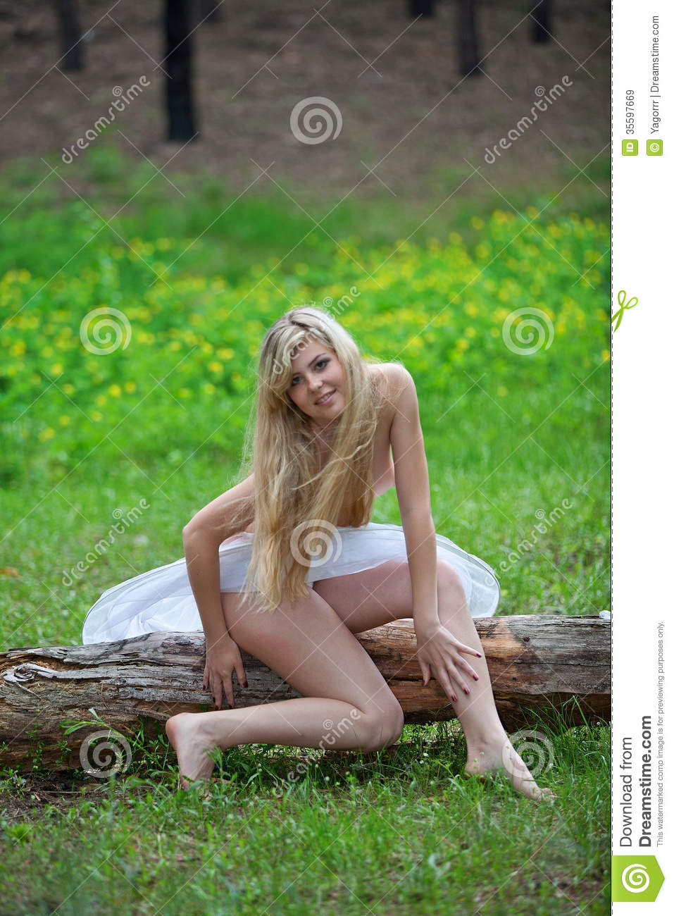 beautiful blonde woman topless sitting on a log in the forest in a