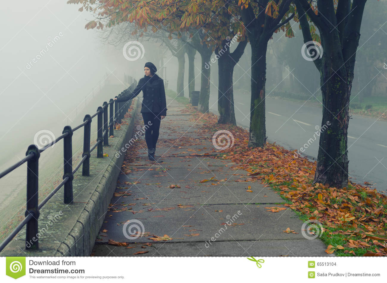 Beautiful girl walking alone on pedestrian walkway in autumn