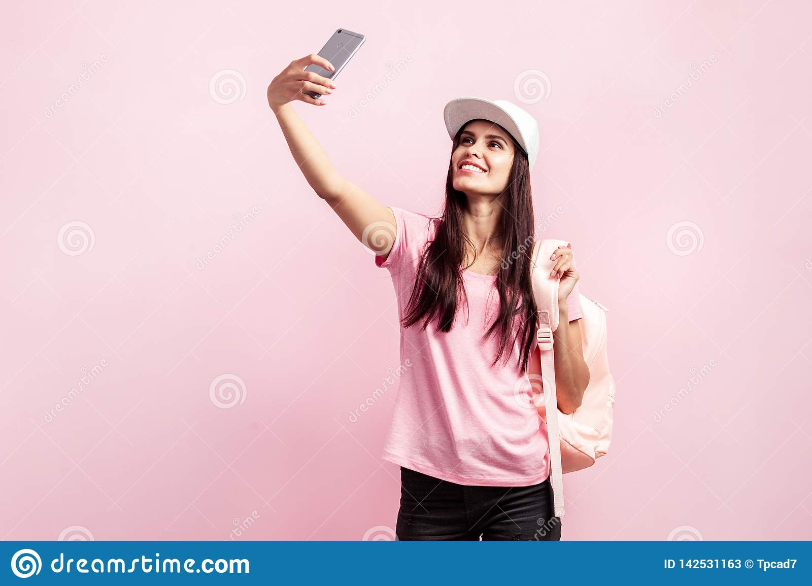 Beautiful girl in white cap and with a backpack on her shoulders dressed in pink t-shirt and black jeans is doing selfie