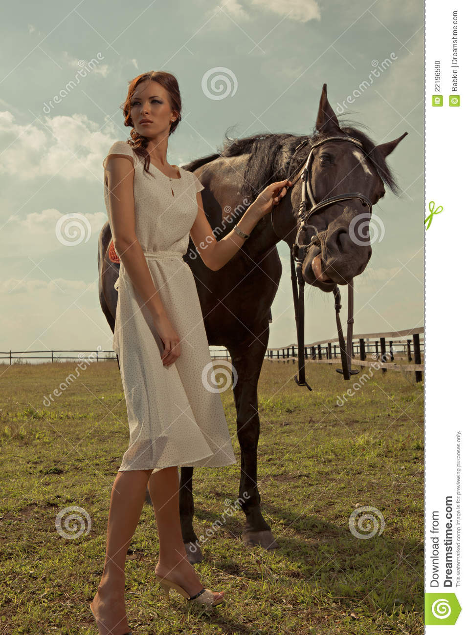 Beautiful girl in a white gown with horse