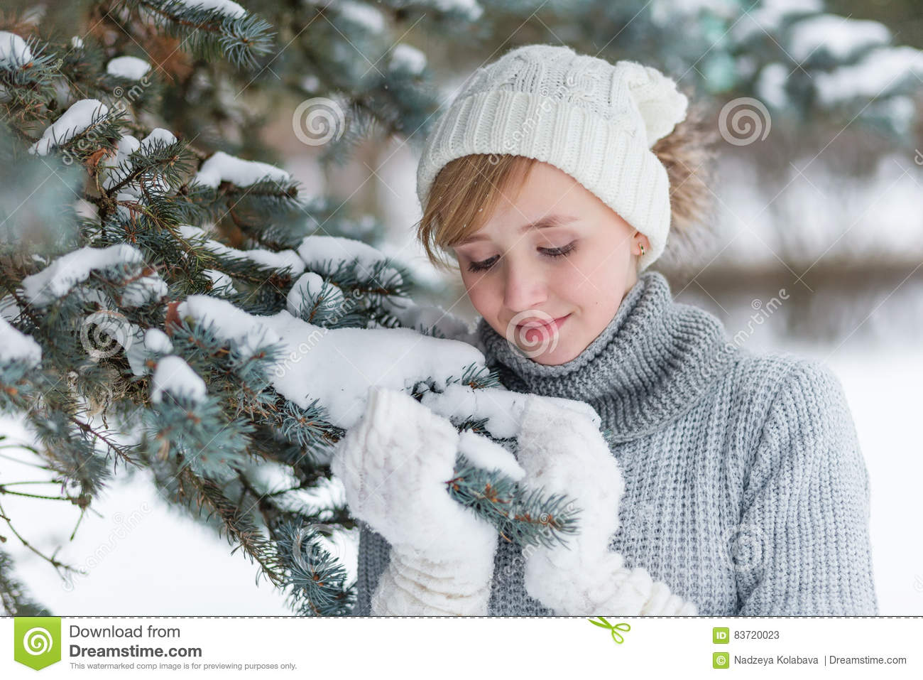 Beautiful Girl In A White Hat And Mittens In The Winter Snowy Fo Stock Photo