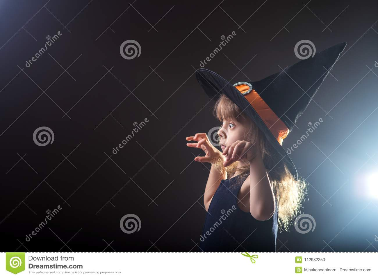 Beautiful girl in a witch hat on a dark background with free space for your text.