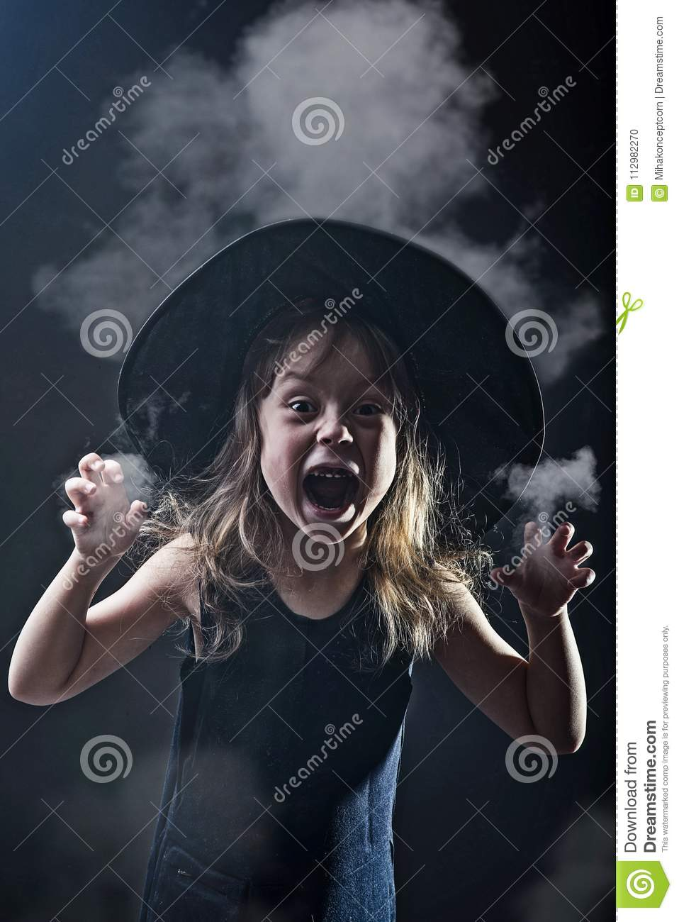Beautiful girl in a witch hat on a dark background in smoke.