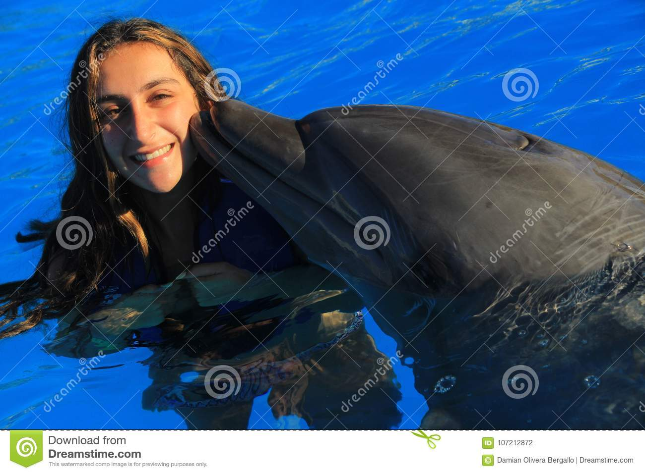 Beautiful girl woman kissing a gorgeous dolphin flipper smiling face happy kid swim bottle nose dolphins