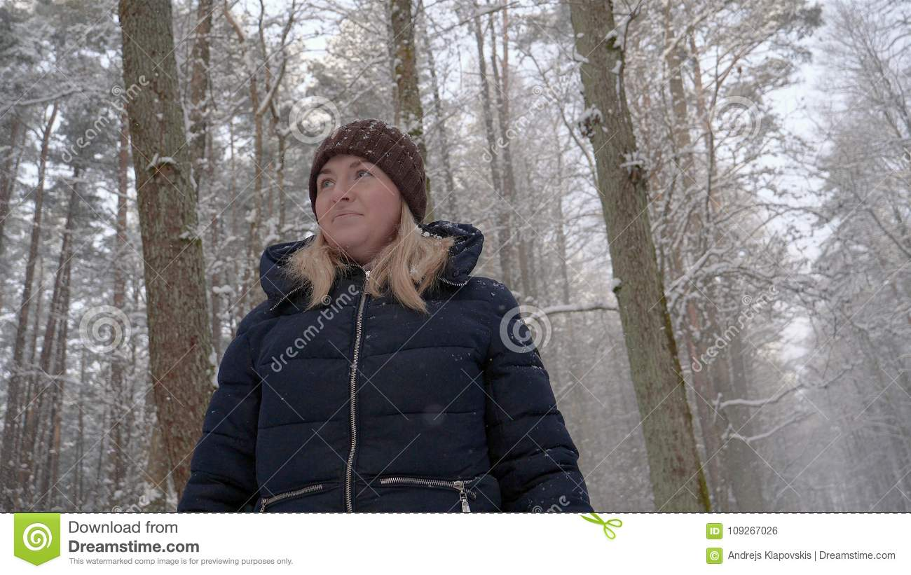A beautiful girl woman walks through the forest, looks around
