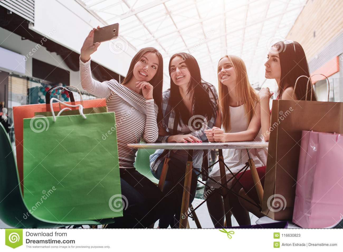 Beautiful girls are sitting at table and talking selfie. Asian girl is holding camera and taking picture of it. There