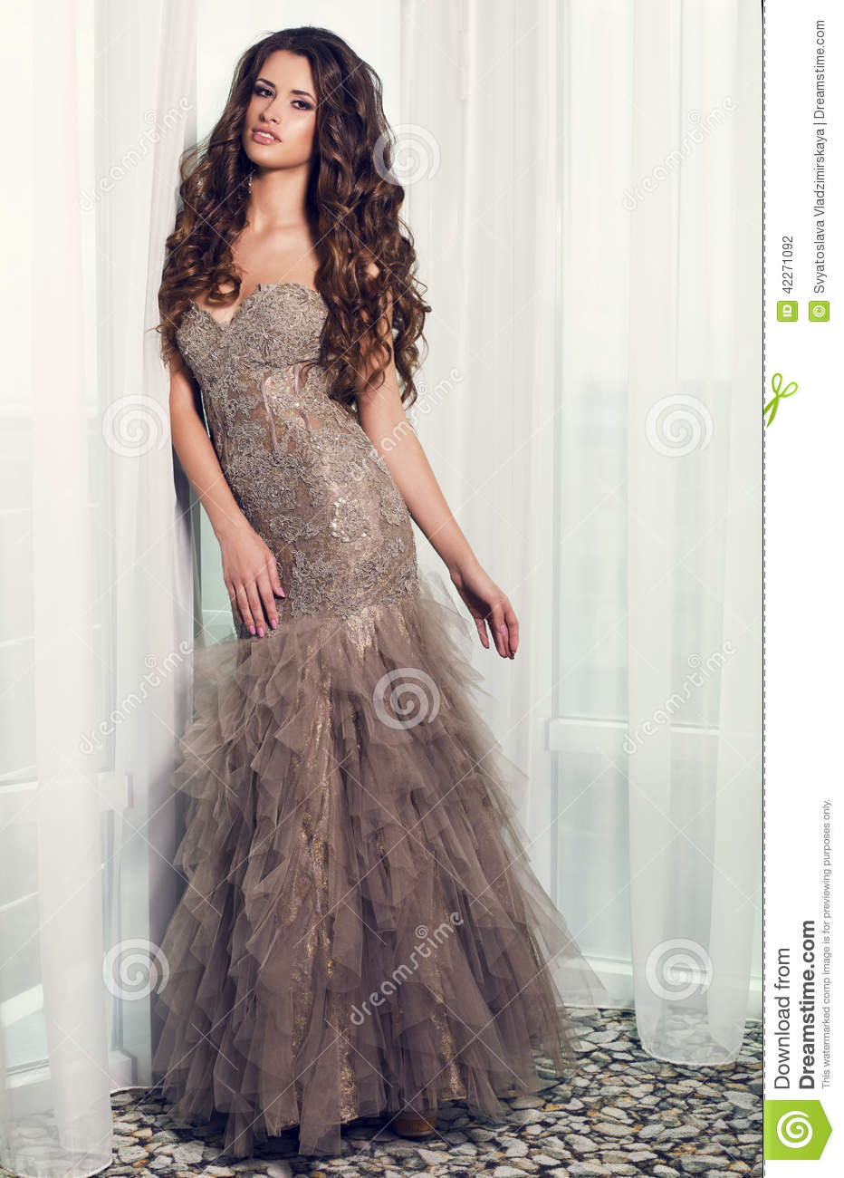 Beautiful glamour woman in luxurious dress posing at bedroom