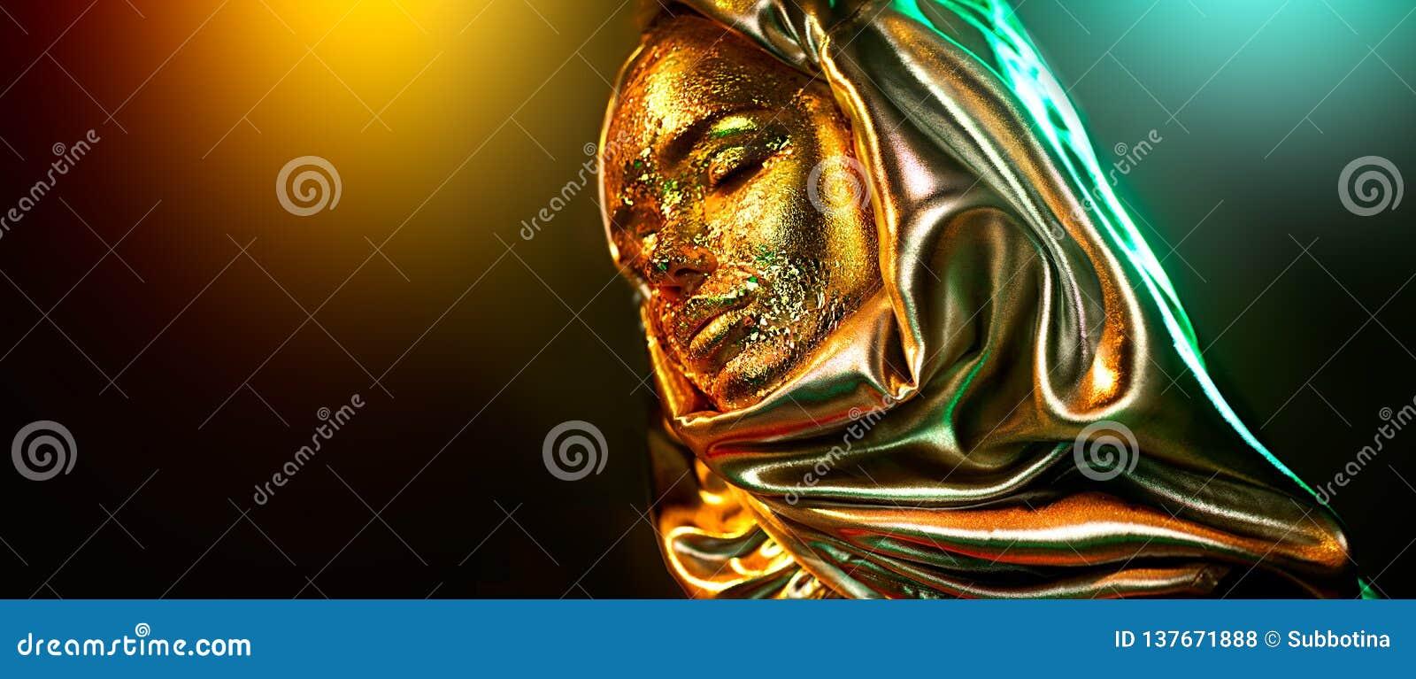 Beautiful gold makeup model girl portrait. Beauty woman with glamour golden foil makeup. Traditional arabian muslim dress, hijab,