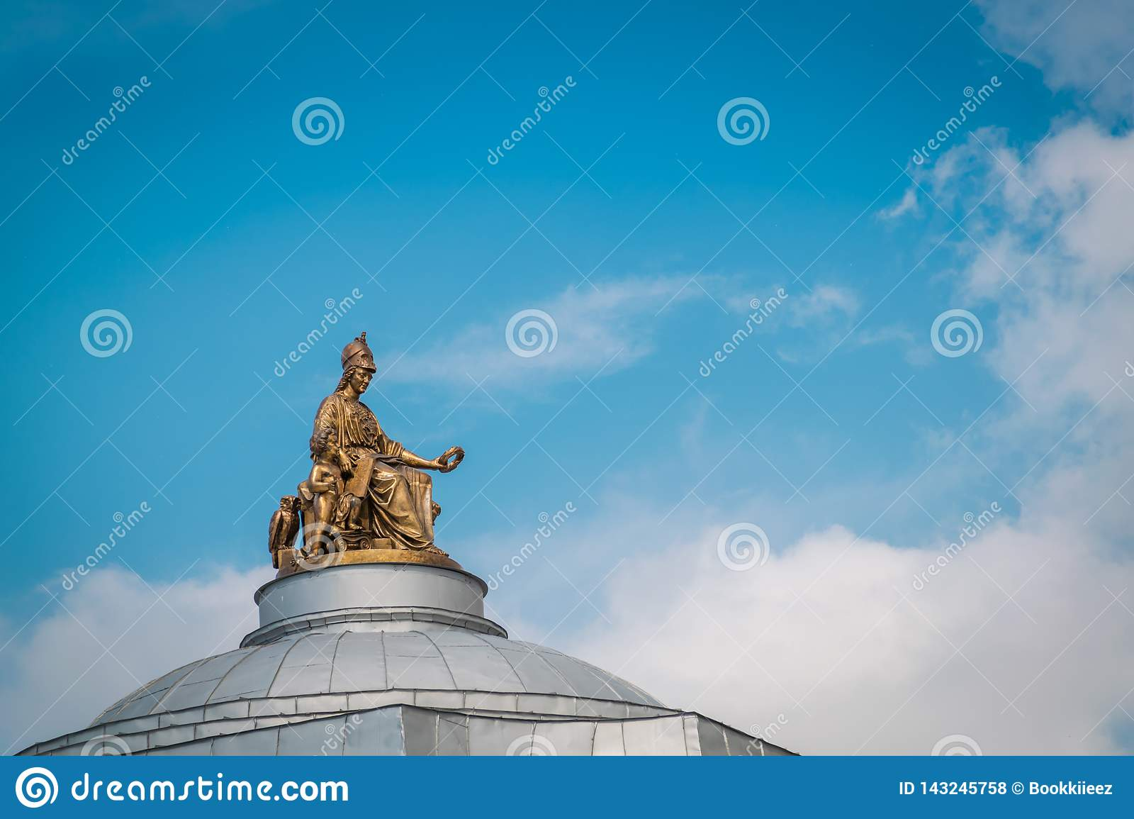The golden statue on roof top of Imperial Academy of Arts building in Saint Petersburg, Russia.
