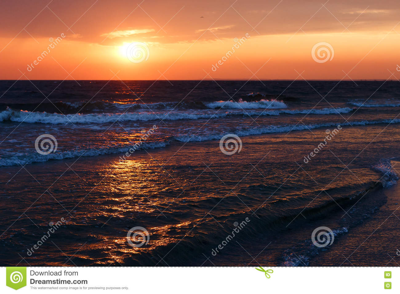 Beautiful golden sunset in the sea with saturated sky and clouds. Reflection in the water. Rocky coastal line. Peaceful serene lan