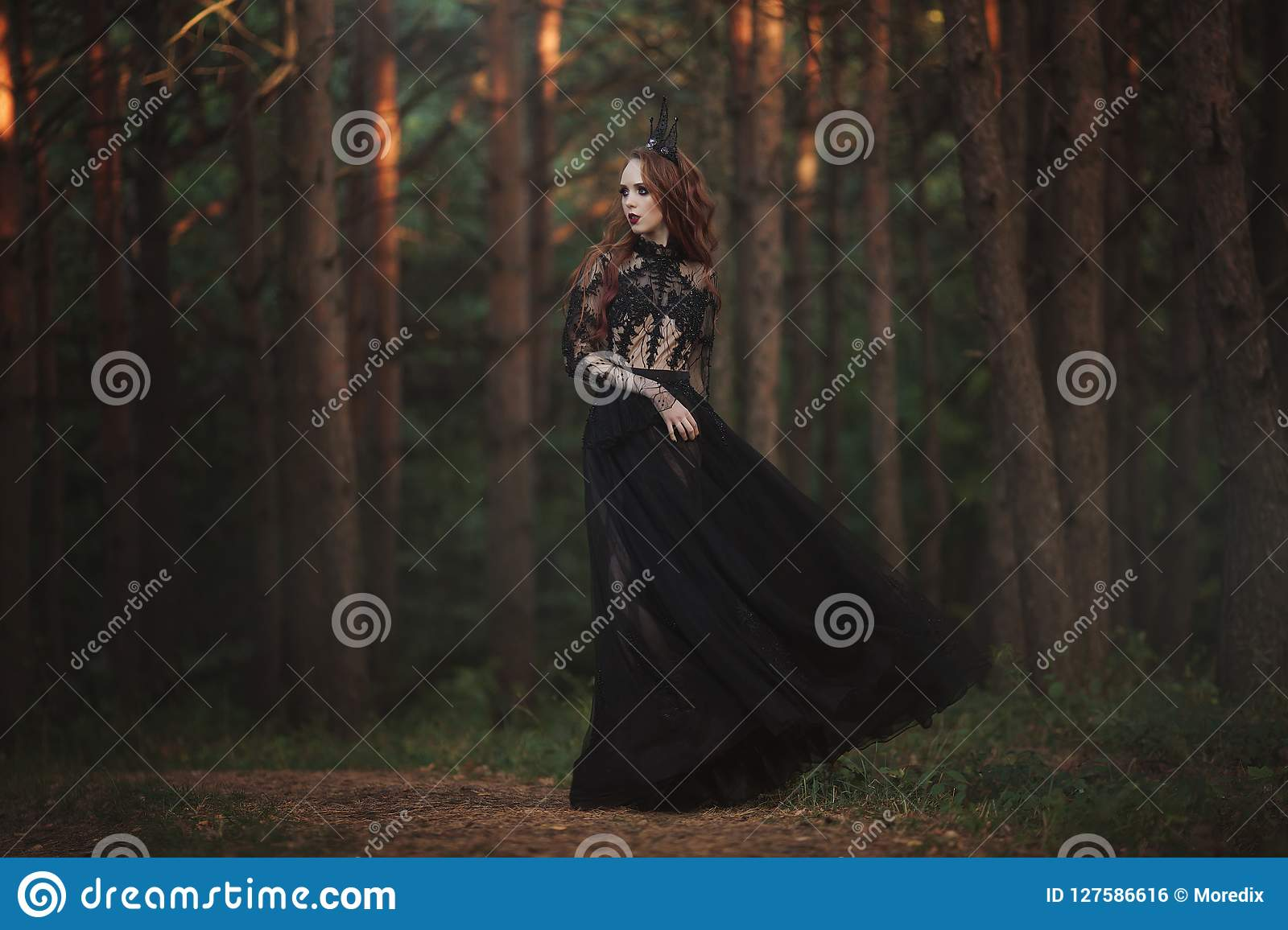 A beautiful gothic princess with pale skin and very long red hair in a black crown and a black long dress in a misty fairy forest.