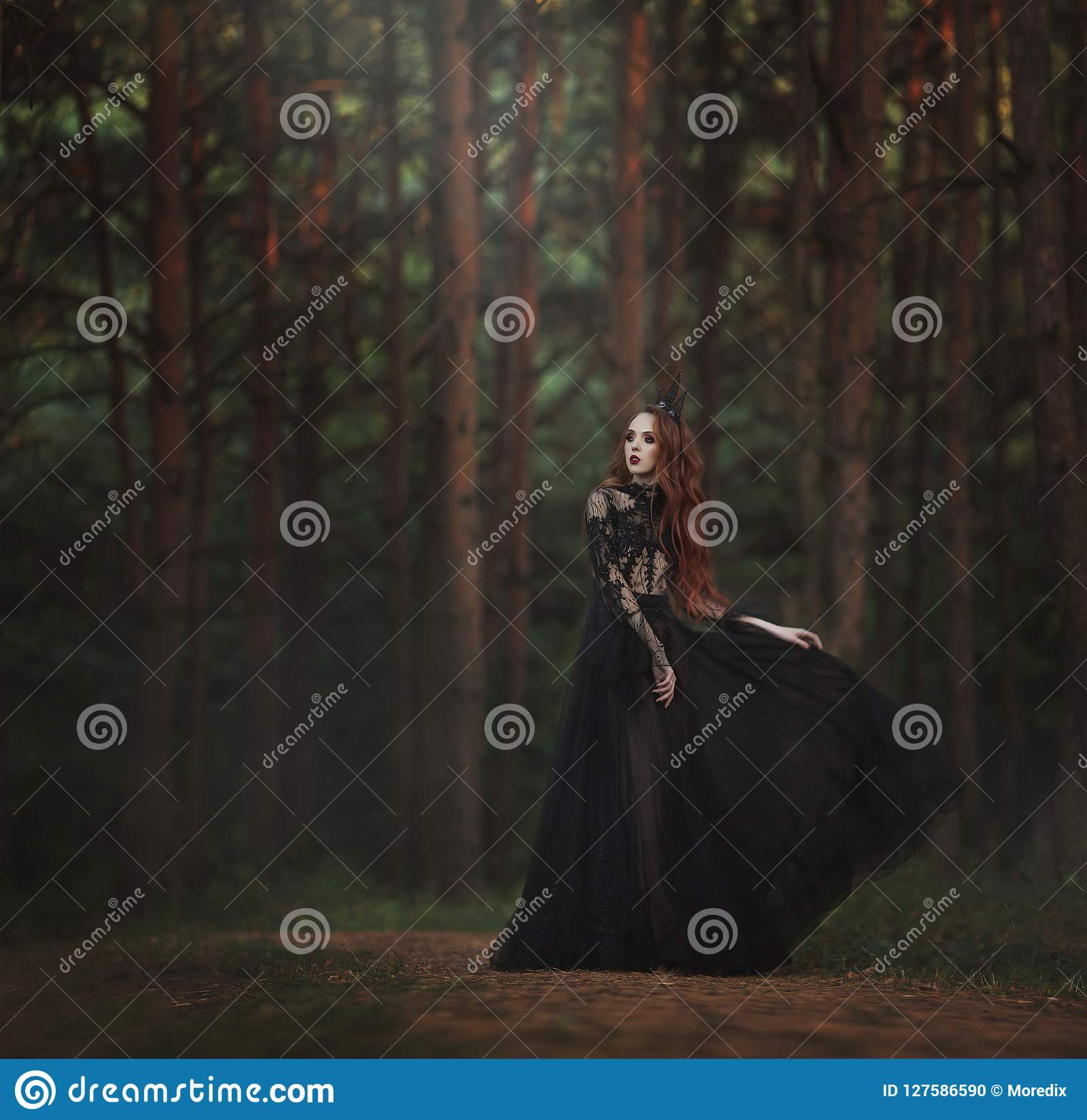 A beautiful gothic princess with pale skin and very long red hair in a black crown and a black long dress walks in a misty fairy-t