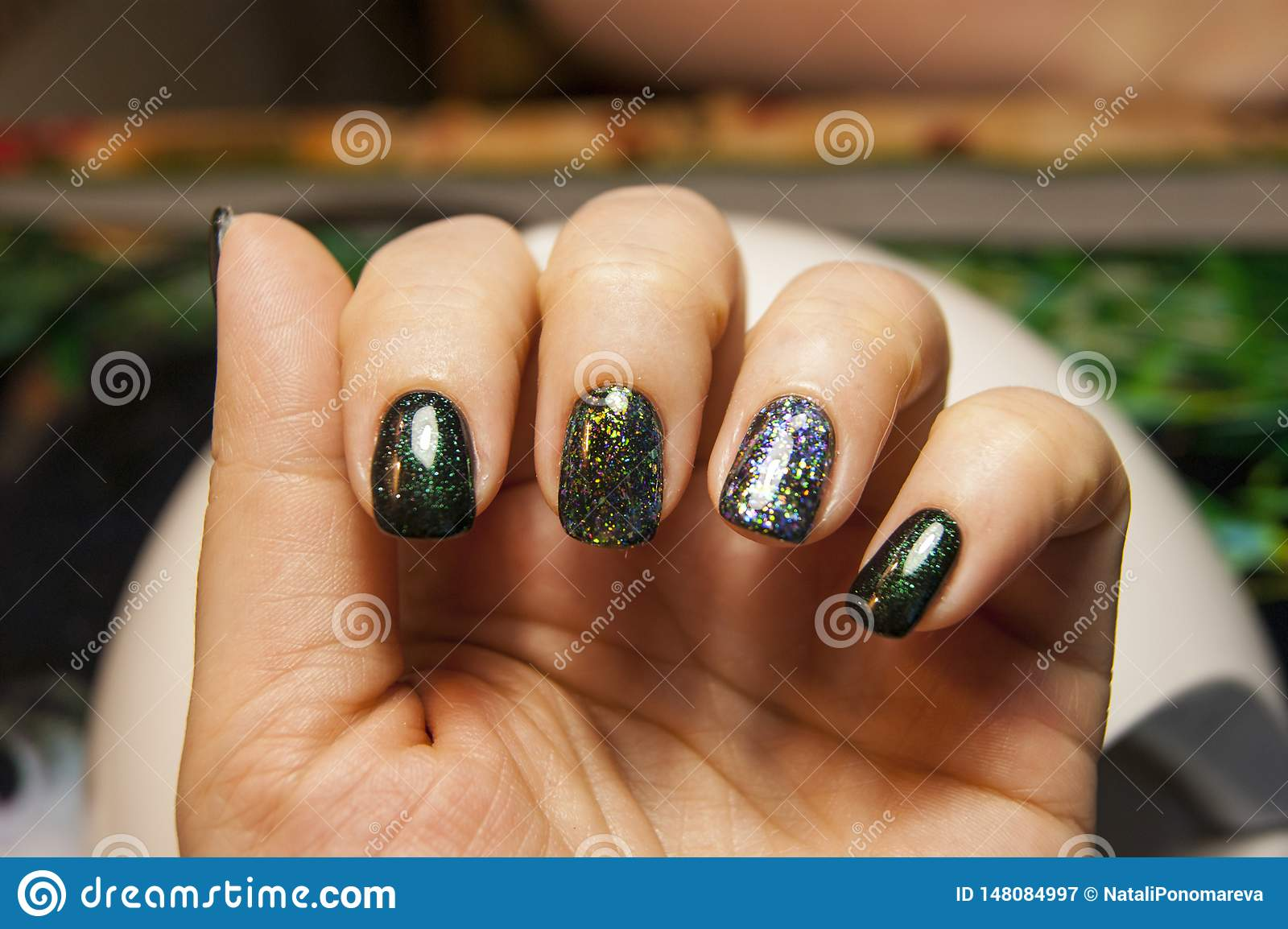 Beautiful green manicure, nail polish on nails of different shades of green, with a slight sheen and large shimmer