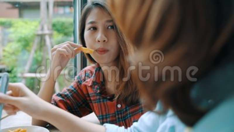 Beautiful happy Asian women lesbian lgbt couple sitting each side eating a  plate of Italian seafood spaghetti and french fries.