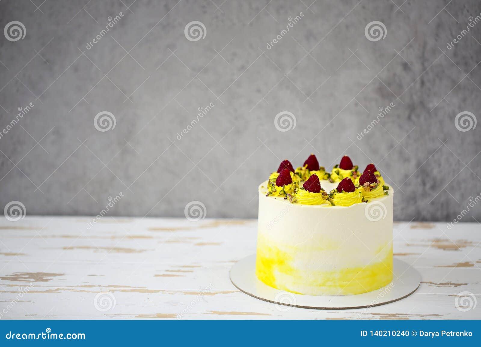 Beautiful happy birthday cake with mascarpone decorated with raspberry, pistachio