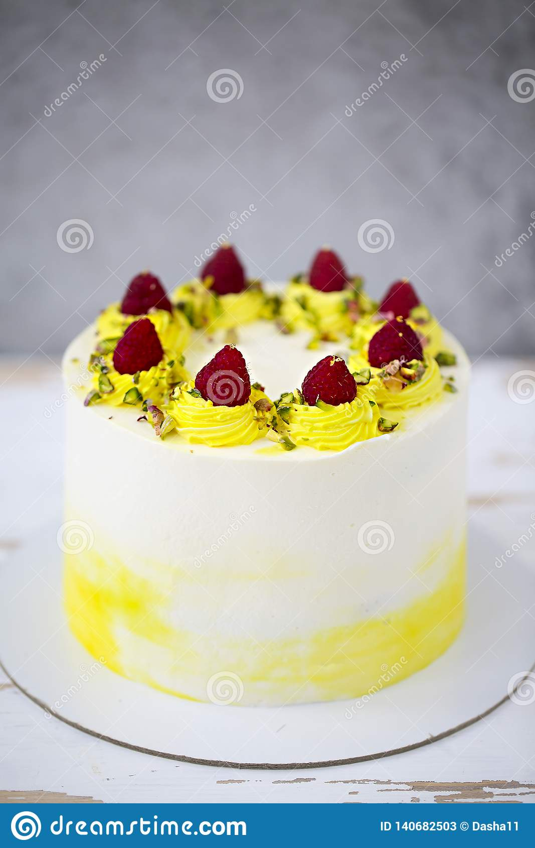 Happy birthday cake with mascarpone decorated with raspberry, pistachio on the cake stand