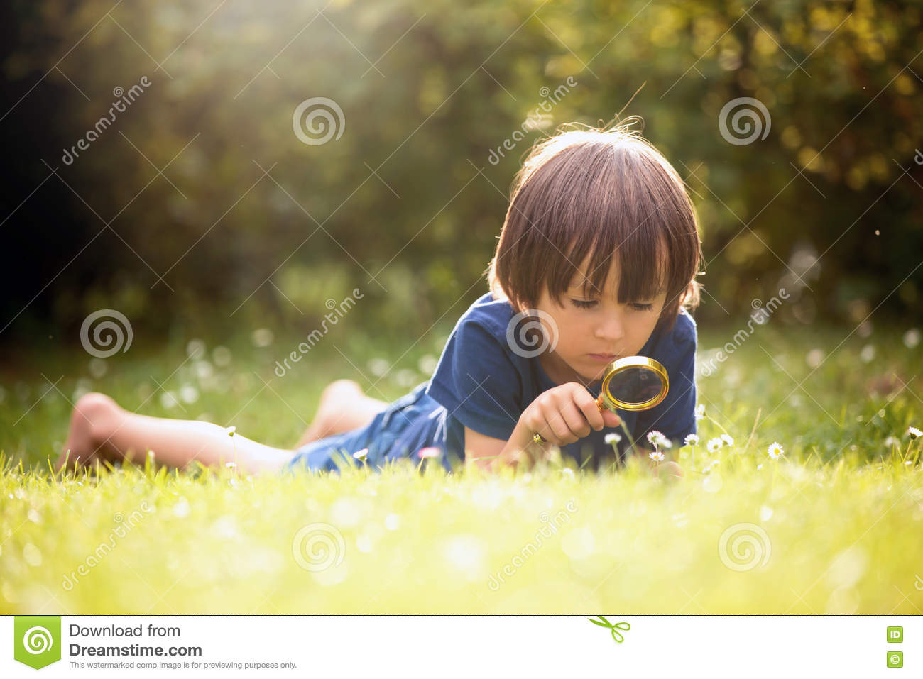Beautiful happy child, boy, exploring nature with magnifying glass, summertime