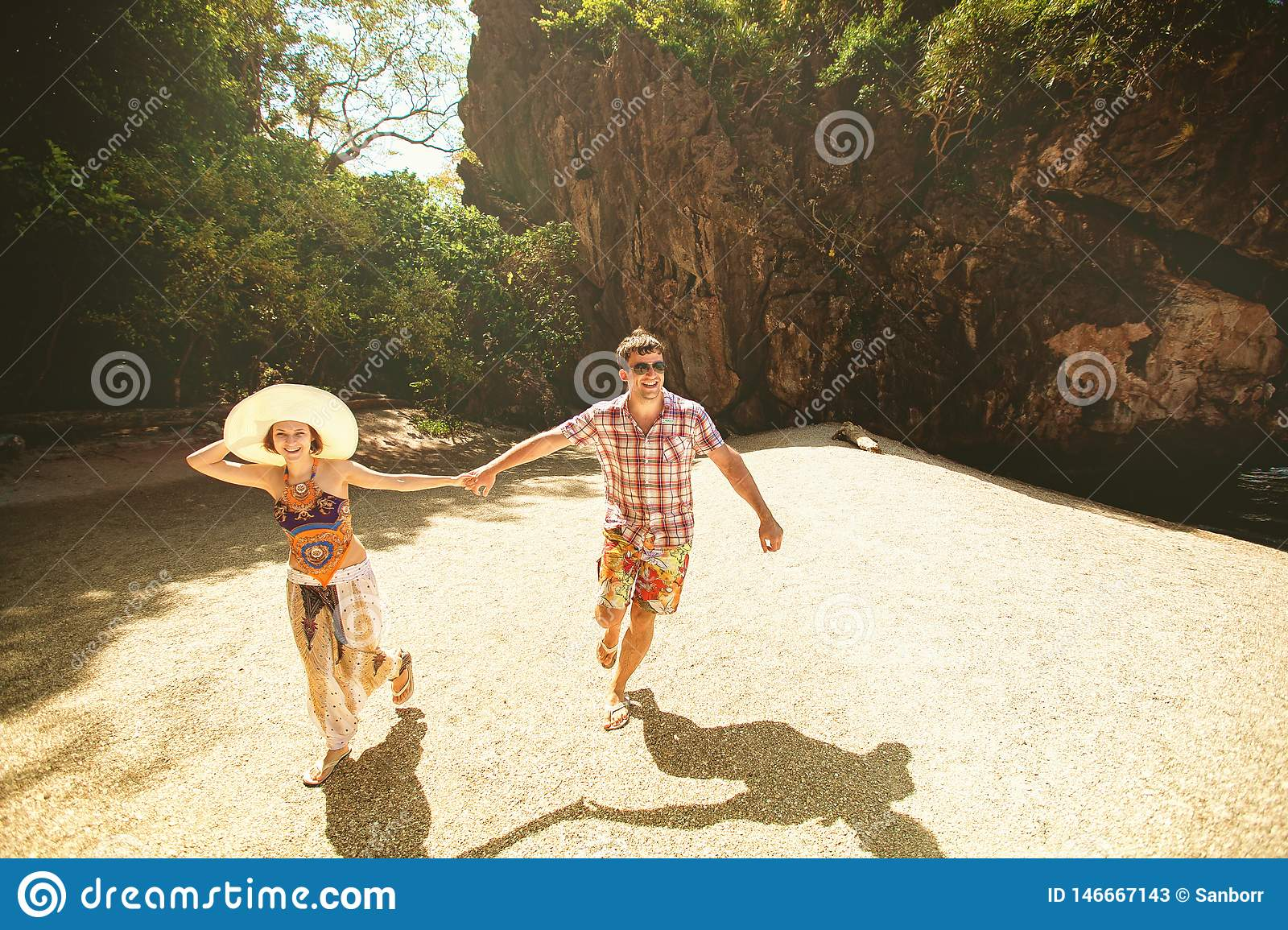 Beautiful happy couple holding hands, walking on the beach with mountains on a Sunny day, outdoors. A girl in a hat and a guy on