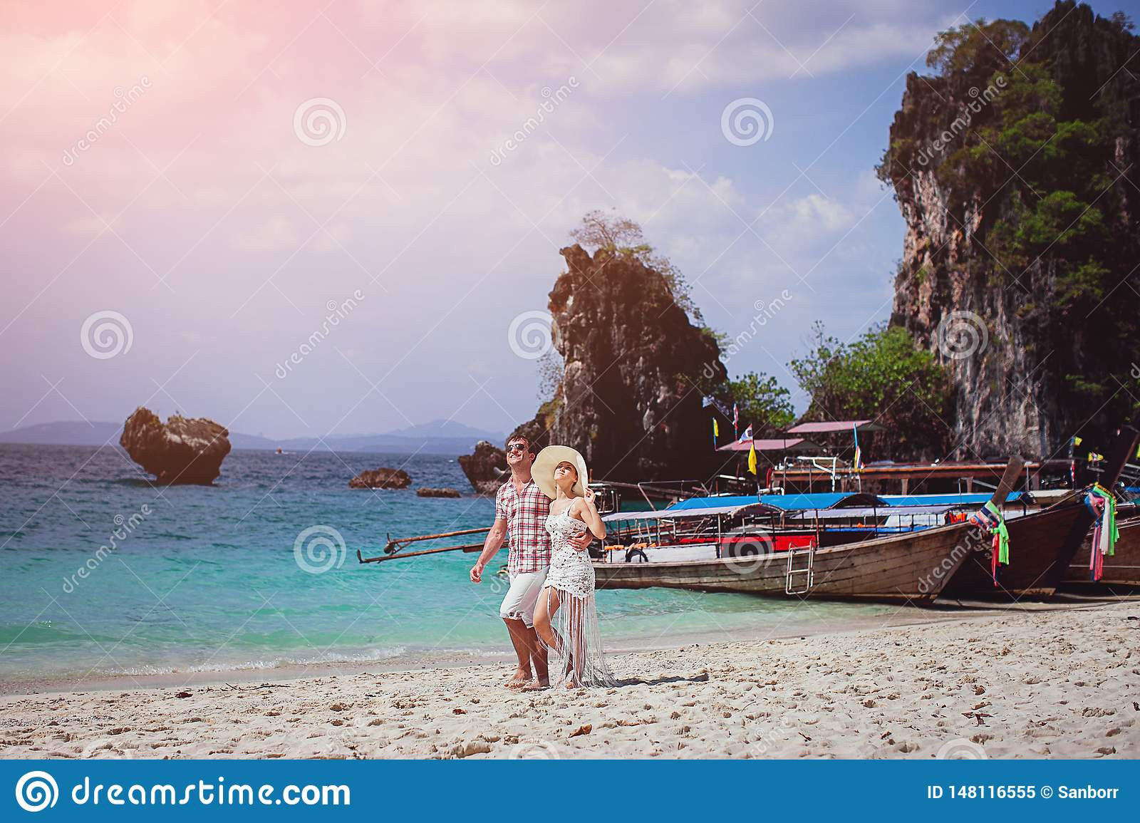 Beautiful happy couple, hugging, walking on the beach against the sea, mountains, gondolas. A girl in a hat and a guy on vacation