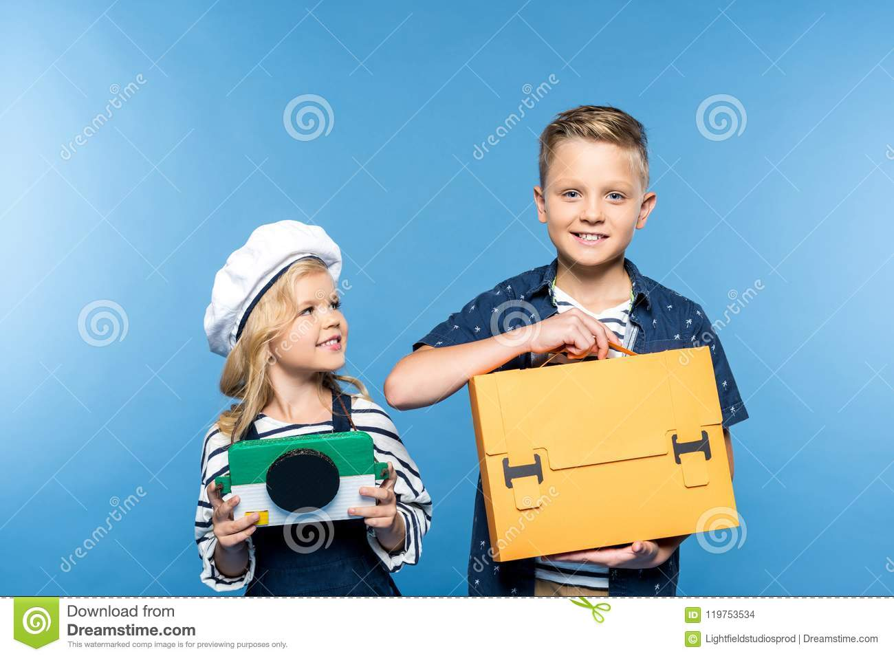 d624836aeb beautiful happy kids holding camera and briefcase isolated on blue