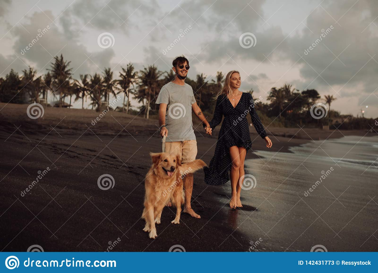 Beautiful happy laugh young hipster couple with golden retriever on beach. ocean an sand. waves. concepte of freedom and