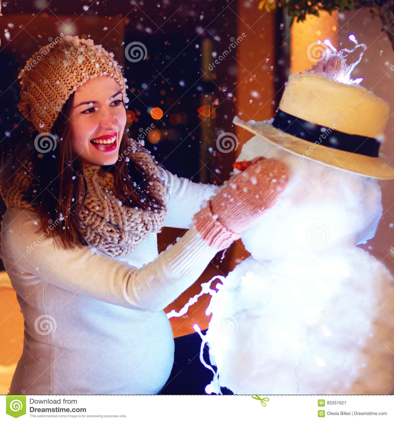 Beautiful happy pregnant woman making snowman under magical winter snow