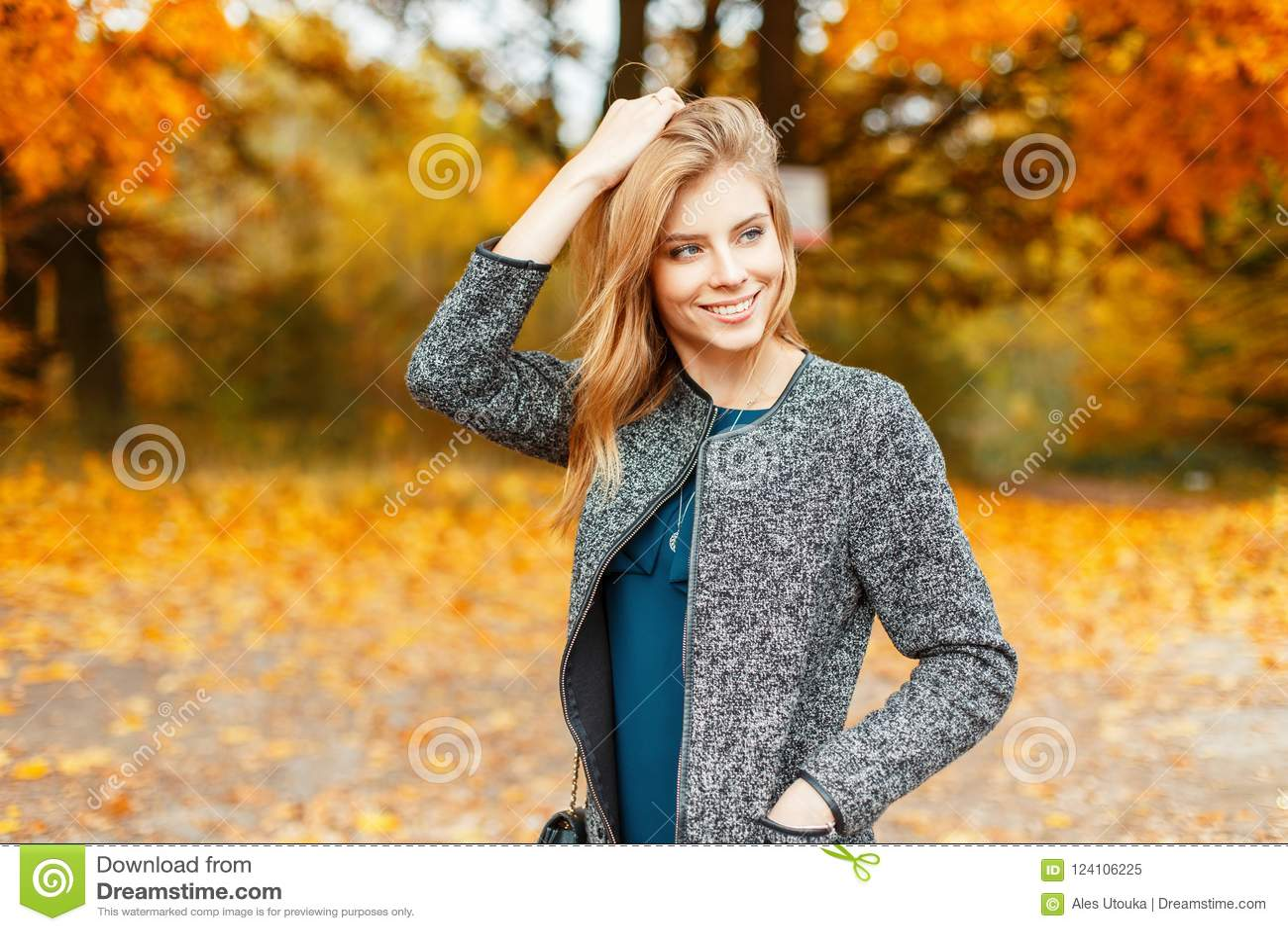 c929455370 Beautiful happy woman in autumn stylish clothes enjoying the weather near  the yellow foliage