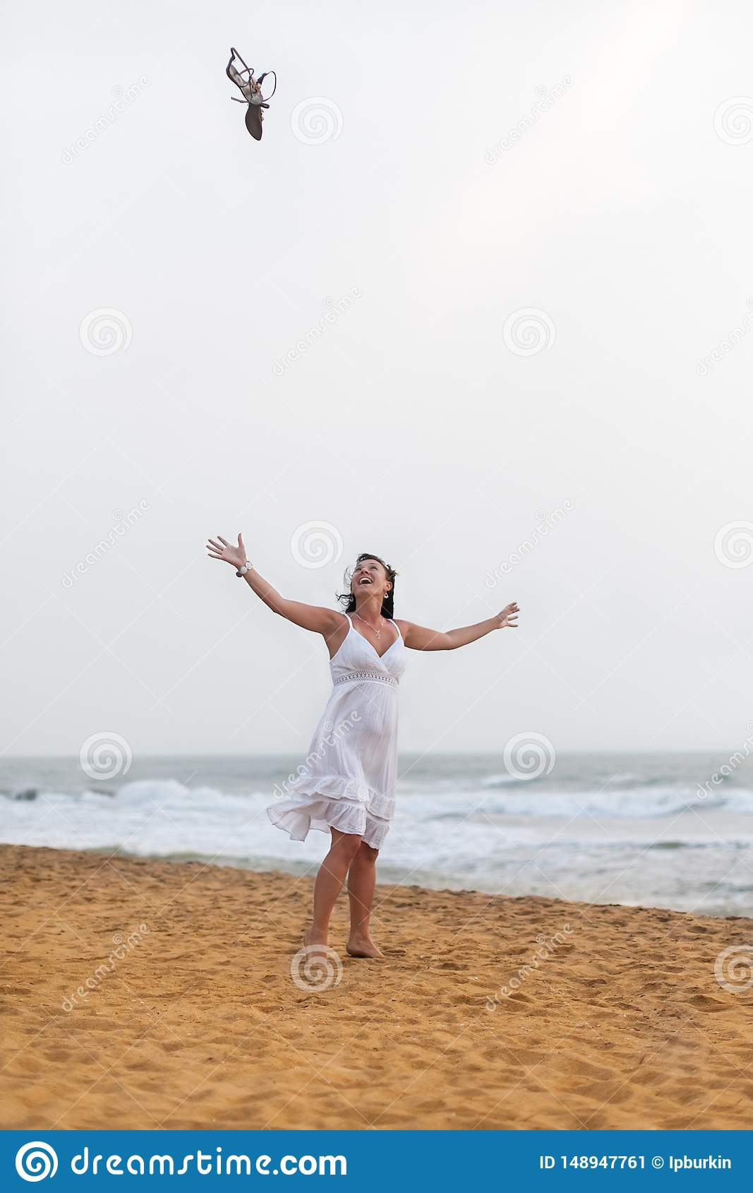 Beautiful happy woman in white dress walking on the sandy beach, throwing his sandals. travel and Summer concept