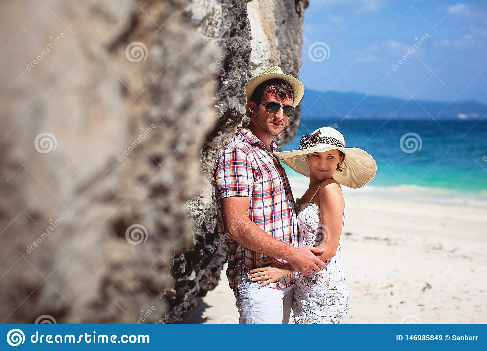 Beautiful happy young couple on the beach, against the sea and mountains on a Sunny day, outdoors. Girl and guy hugging on