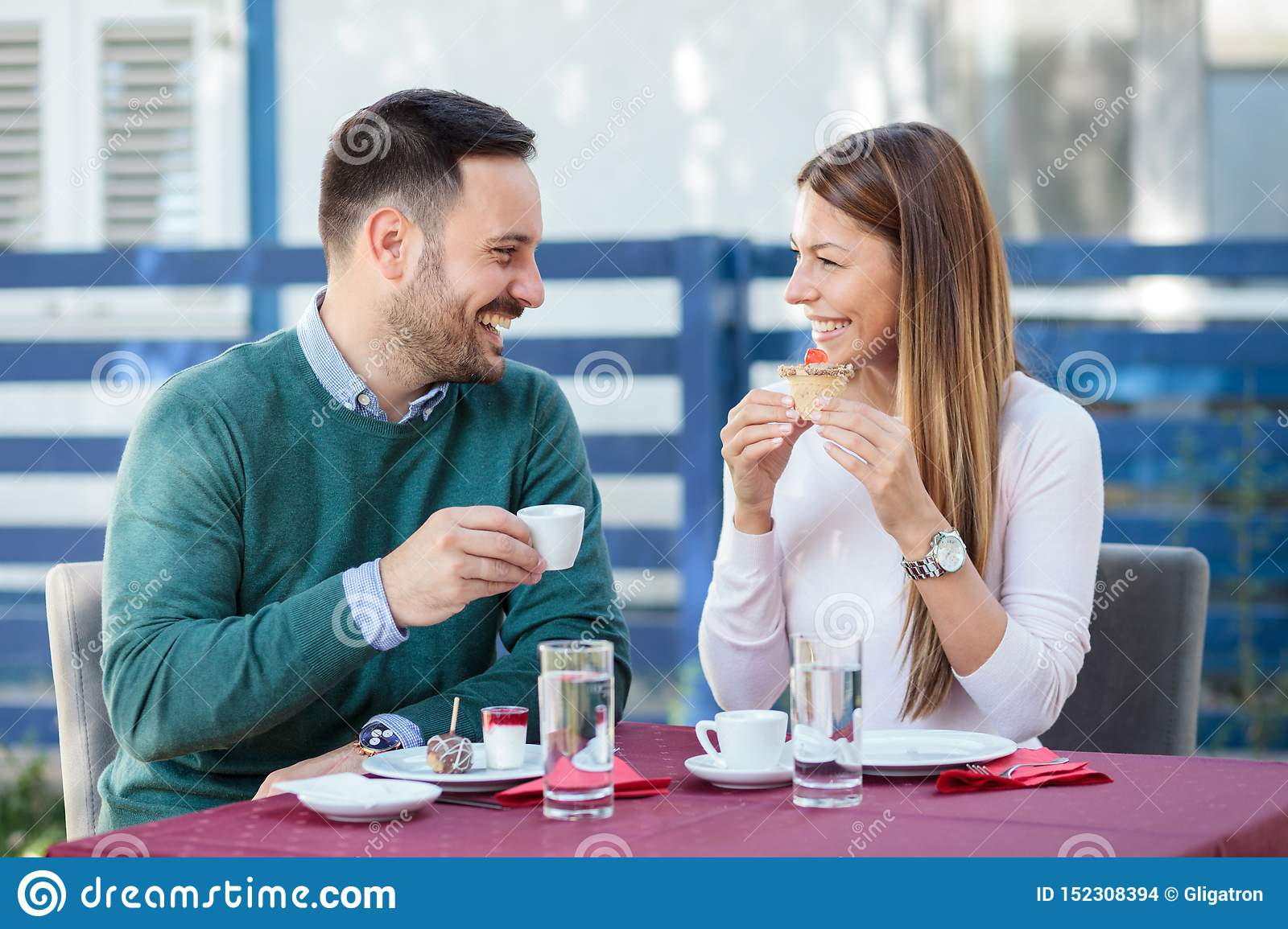Beautiful happy young couple eating cakes and drinking coffee in a restaurant