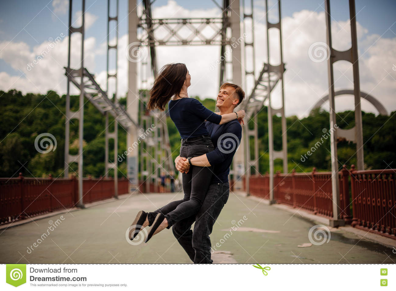 Beautiful happy young couple of man and woman spinning outdoor on bridge