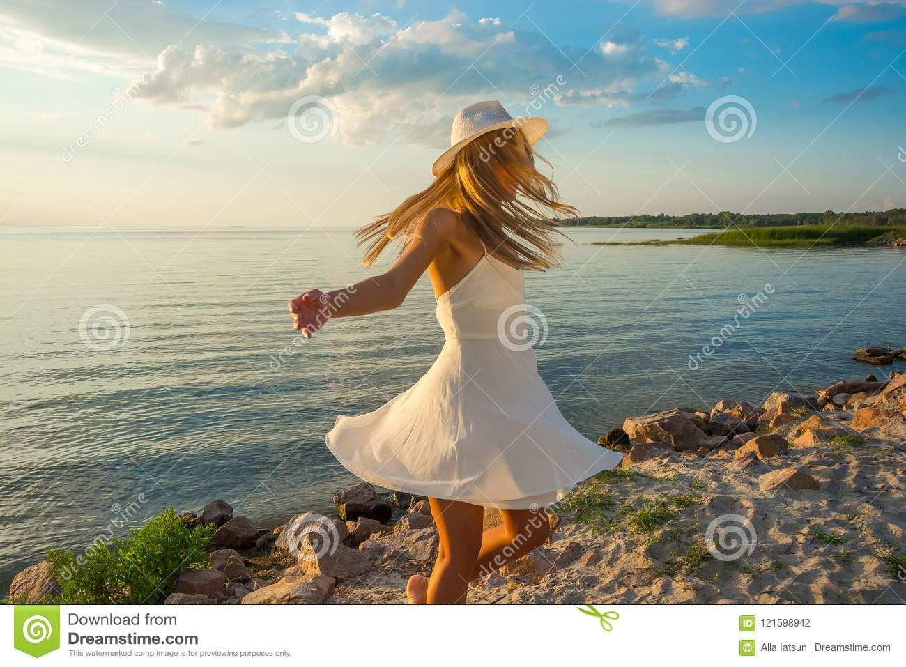 b6b14d3c59f Beautiful happy young woman in white summer satin dress and in a hat whirls  at the sea background at sunset. Her long hair covers her face