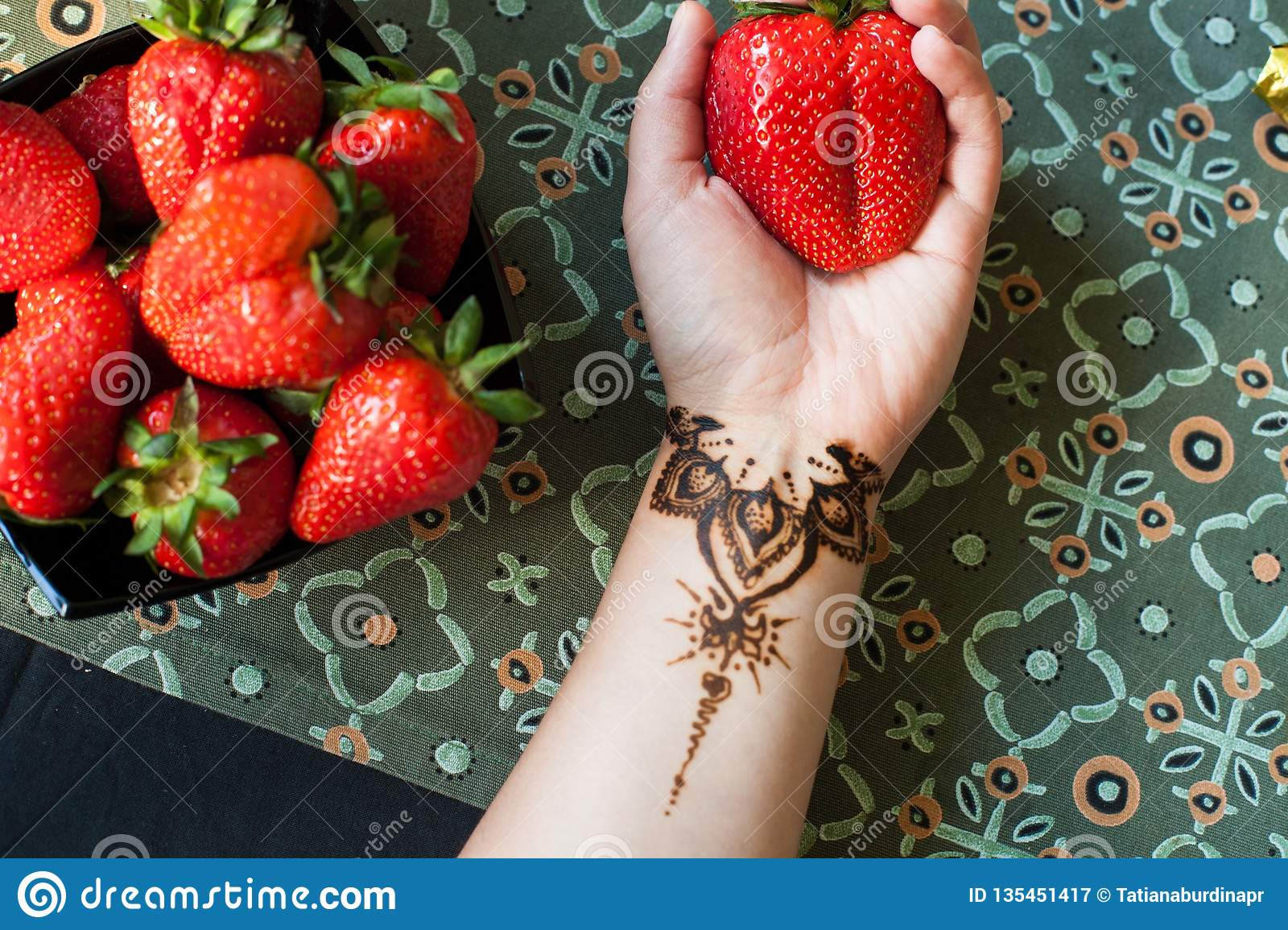 Female hand with arabic or indian mehendi and giant strawberry. Beauty and fashion concept. traditional patterns