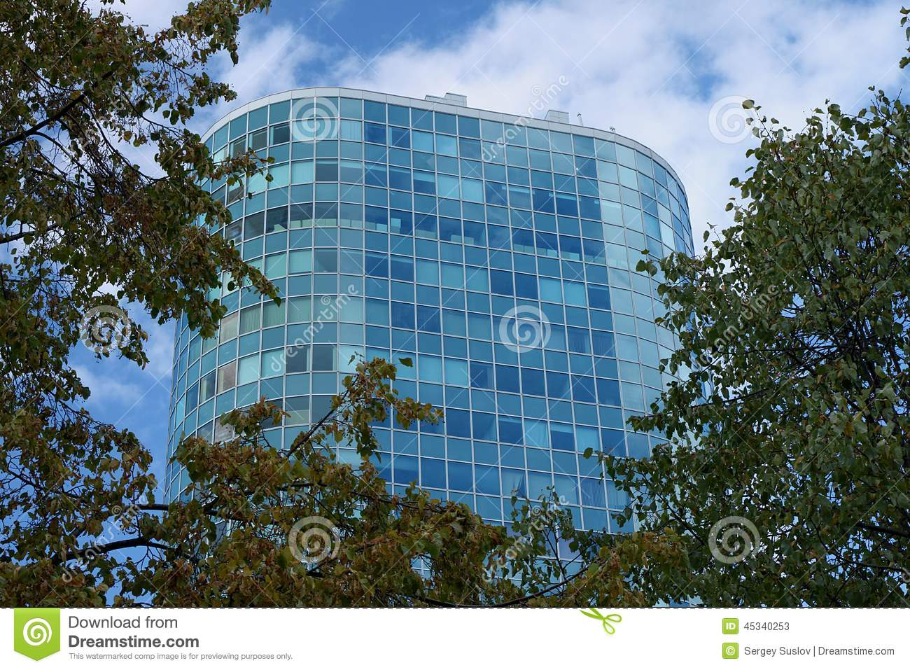 A beautiful high blue glass office building surrounded by trees