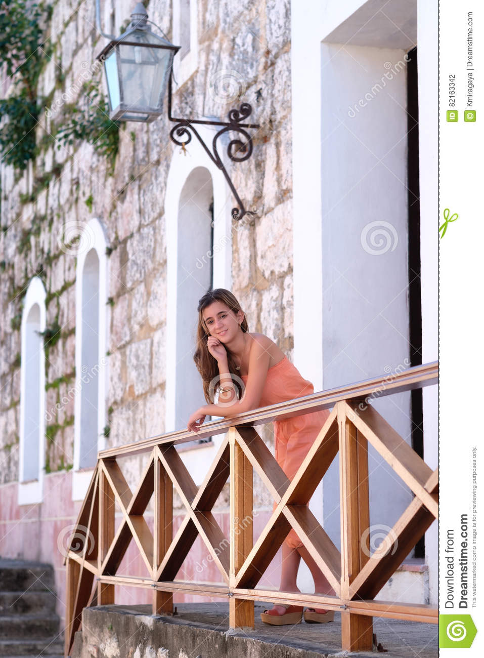 Beautiful hispanic teenage girl standing on a balcony