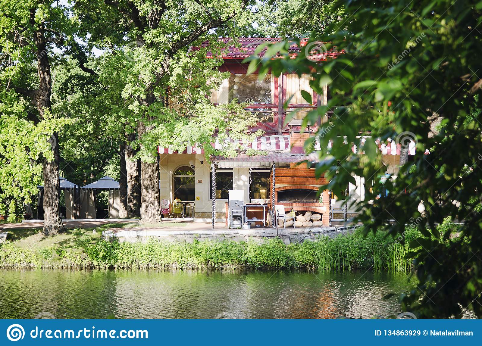 A beautiful house on the shore of a pond among trees. summer day
