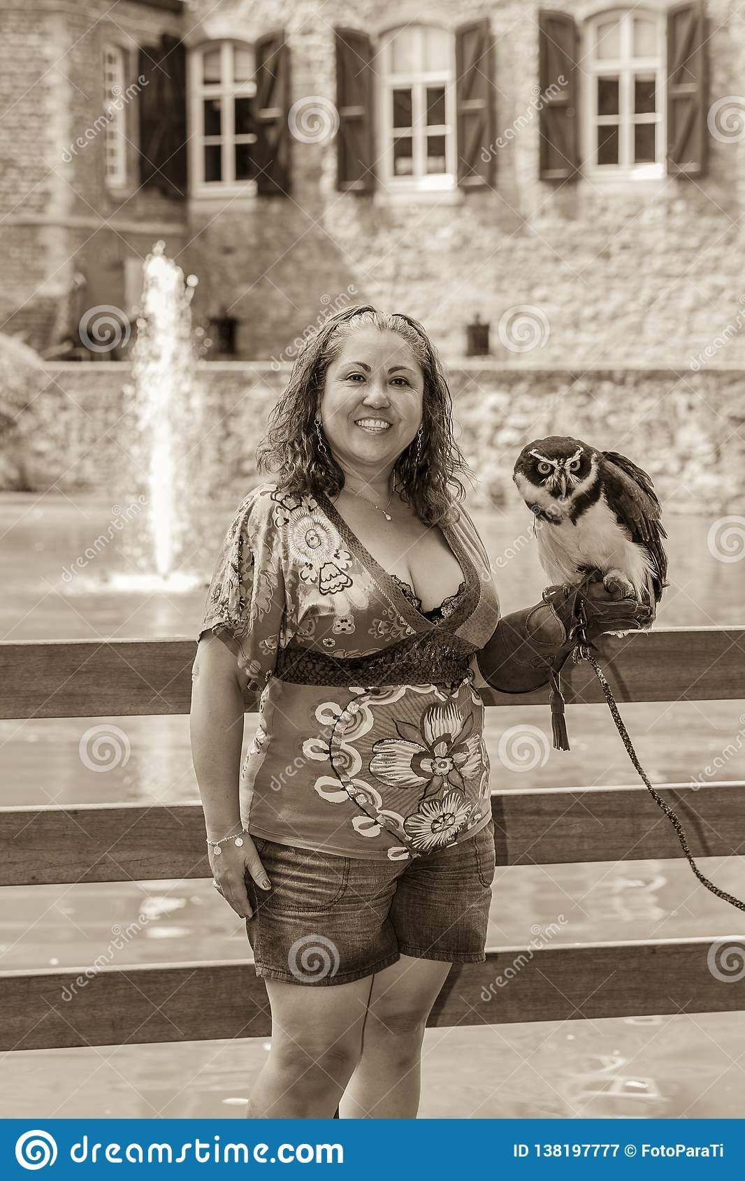 Beautiful image black and white of a smiling woman posing with an owl in her hand