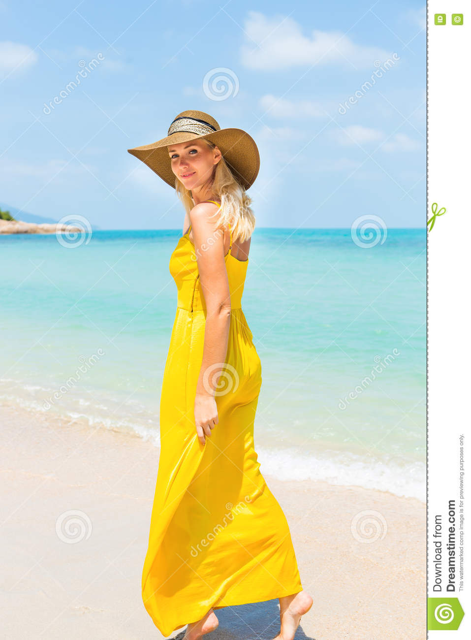 Carefree beautiful fashion blonde woman in beach straw hat and long yellow  dress flying in the wind walking barefoot by sand of tropical beach. Natural  ... c7d12bdc6a49
