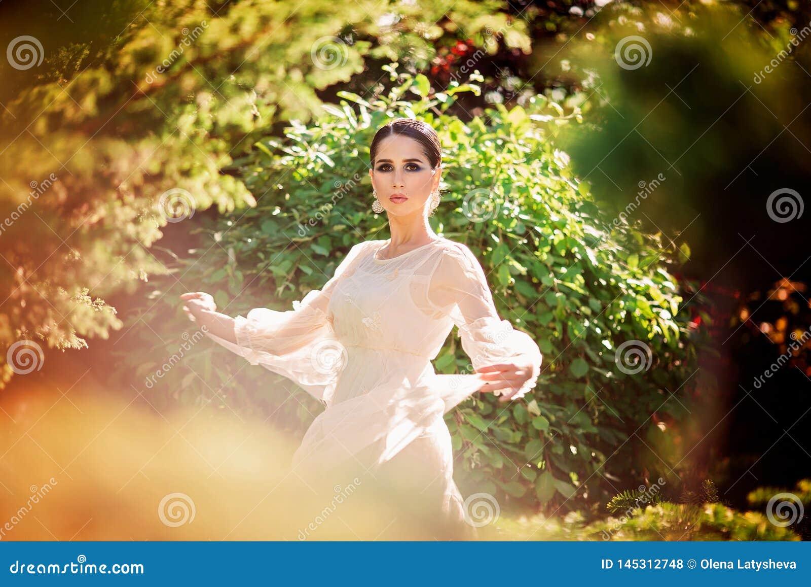 Beautiful lady dancing in sunlight garden