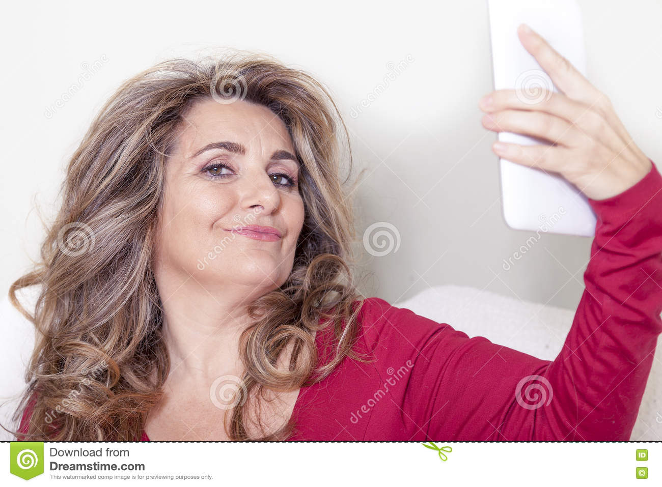 Beautiful lady with red dress takes a selfie