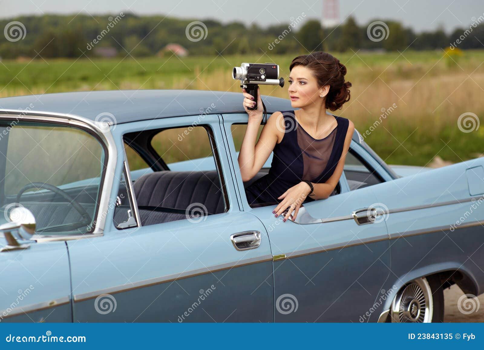 Beautiful lady with a retro movie camera