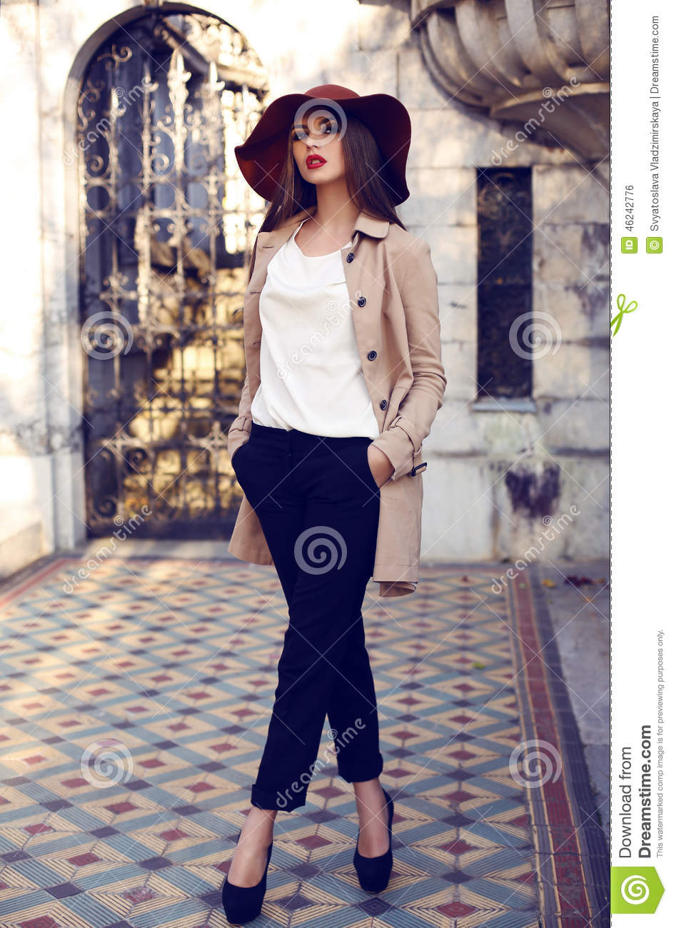 Beautiful ladylike woman in elegant fashion clothes posing in palace