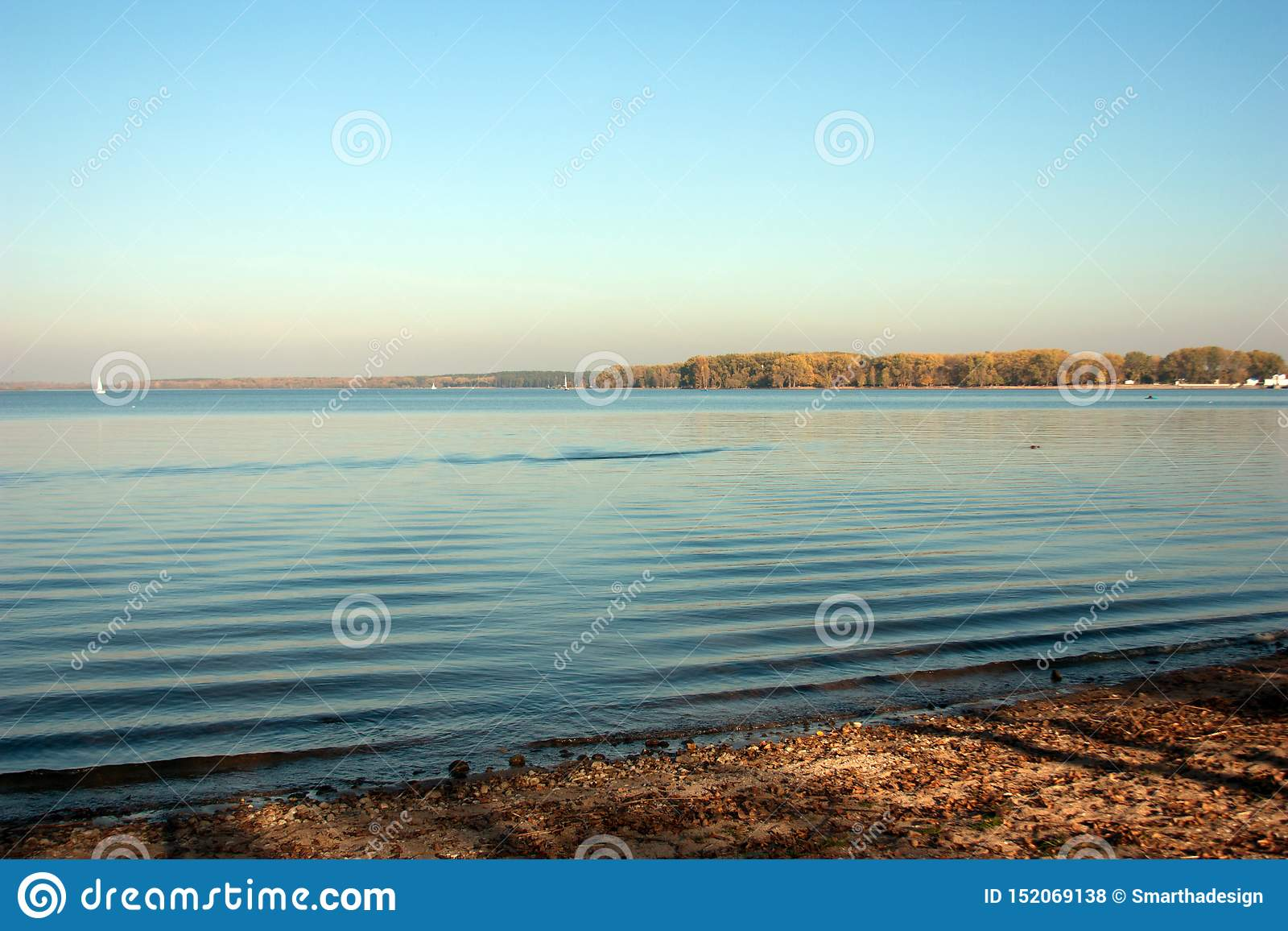 Beautiful lake landscape, and sunset. Blue waves and horizon line on water. Beautiful background