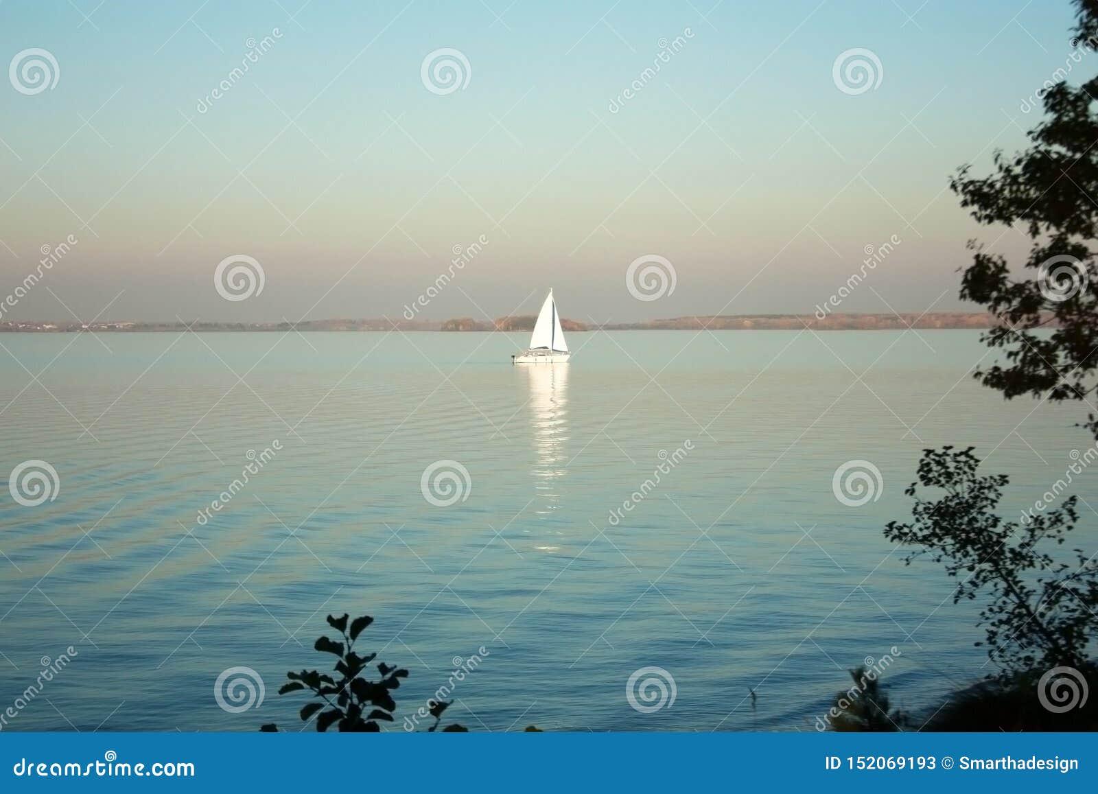 Beautiful lake landscape, yacht, and sunset. Blue waves, boat and horizon line on water. Beautiful background