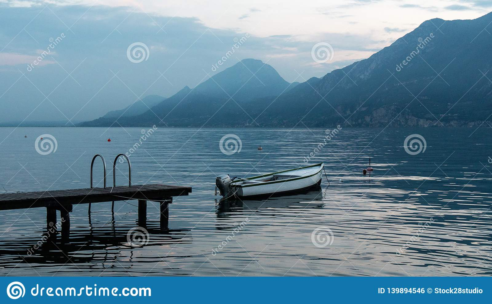 Beautiful landscape on lake Garda in Italy. Boat near the pier on the water surface of the water. The blue hues of the