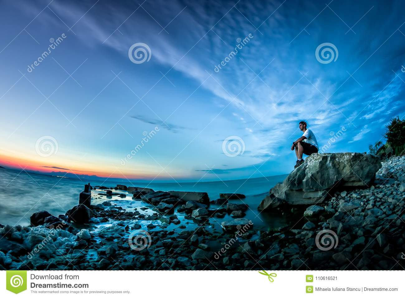 Beautiful landscape with sunset over the lake and a young man sitting on a rock