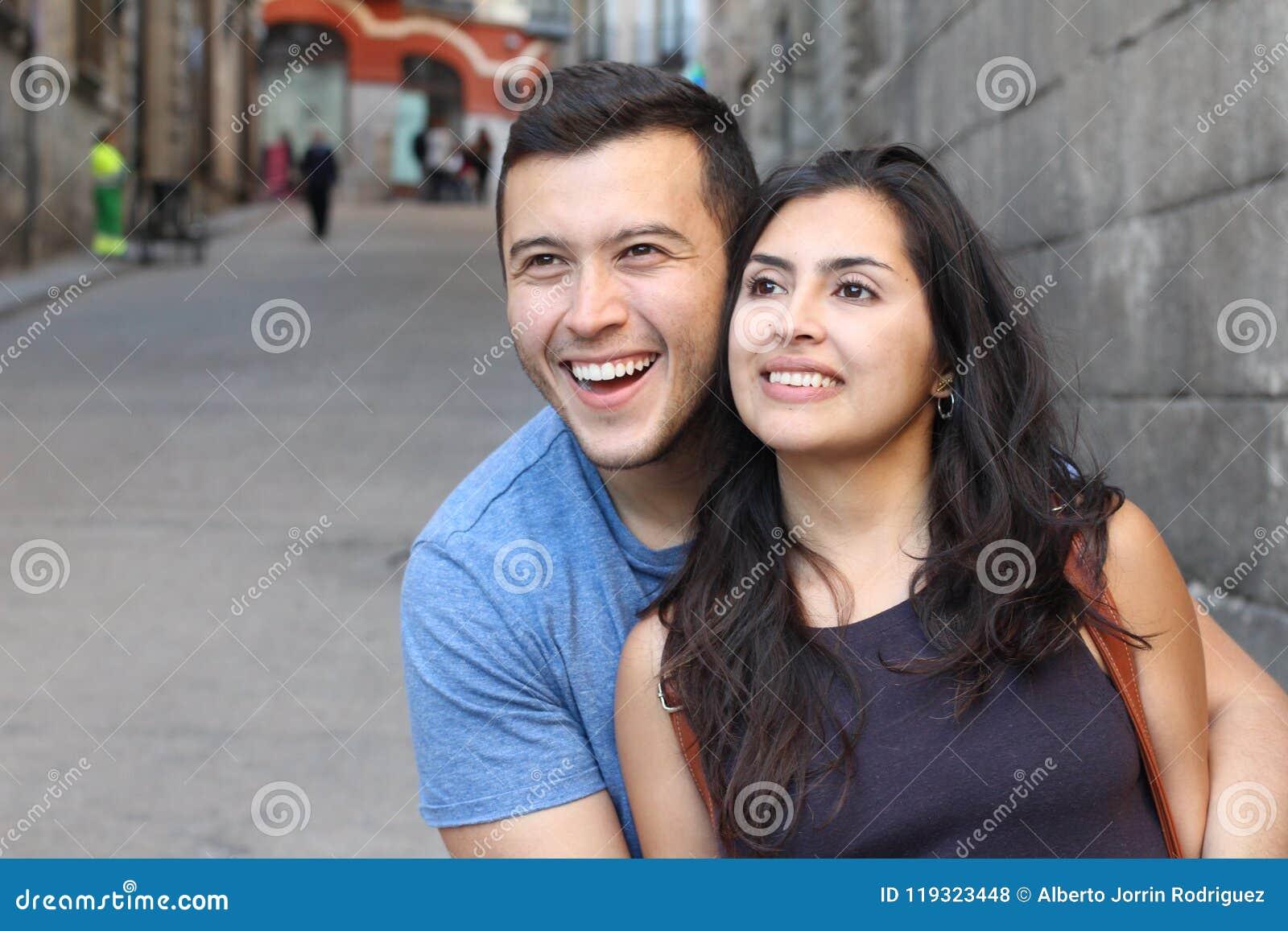 Beautiful latino couple smiling while looking away