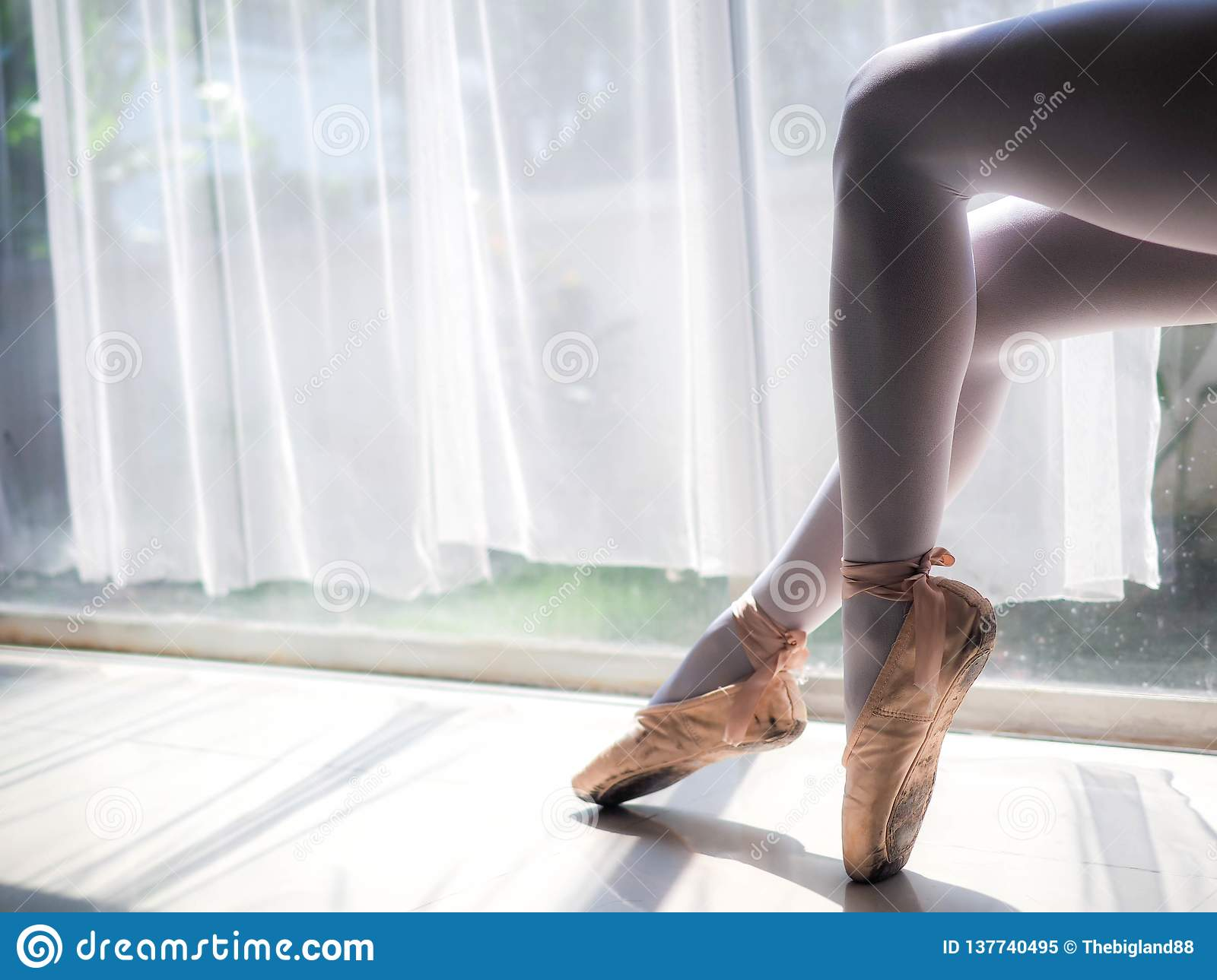 Beautiful legs of young ballerina. Ballet practice. Beautiful slim graceful feet of ballet dancer